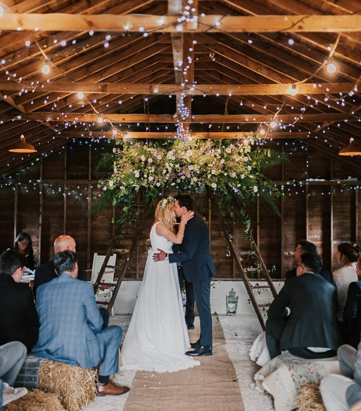 Victoria and Stevie exchanging vows in the rustic barn